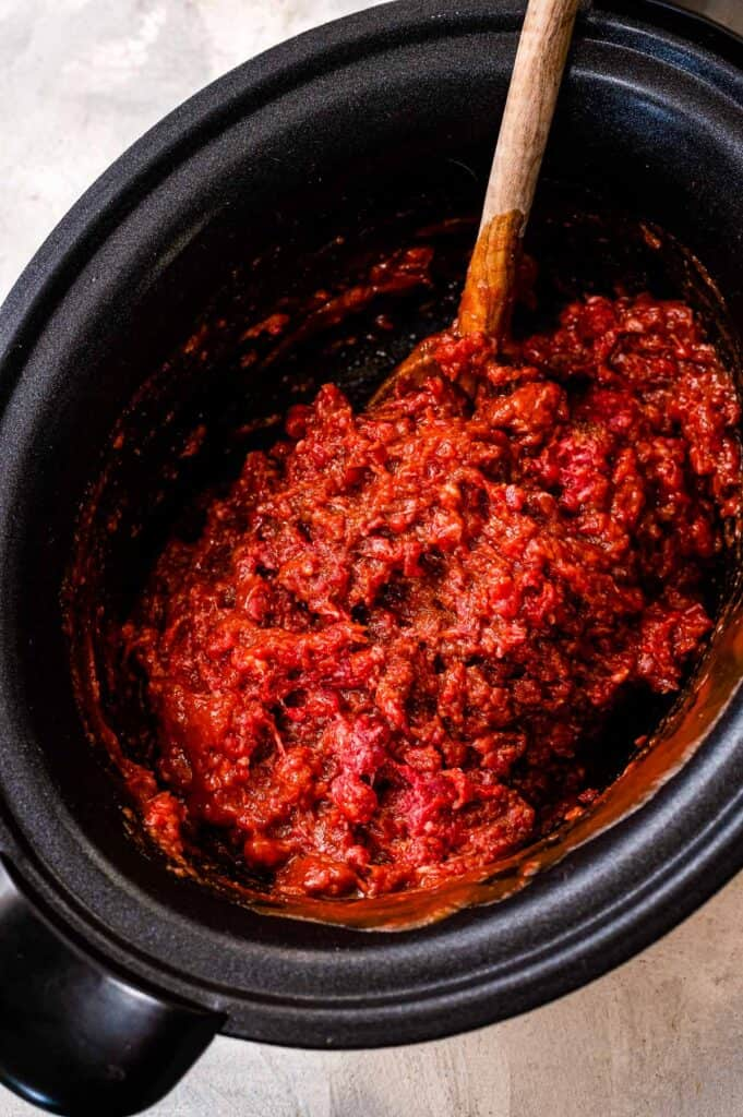 Black crock pot with ground beef, tomato sauce and spices mixed together