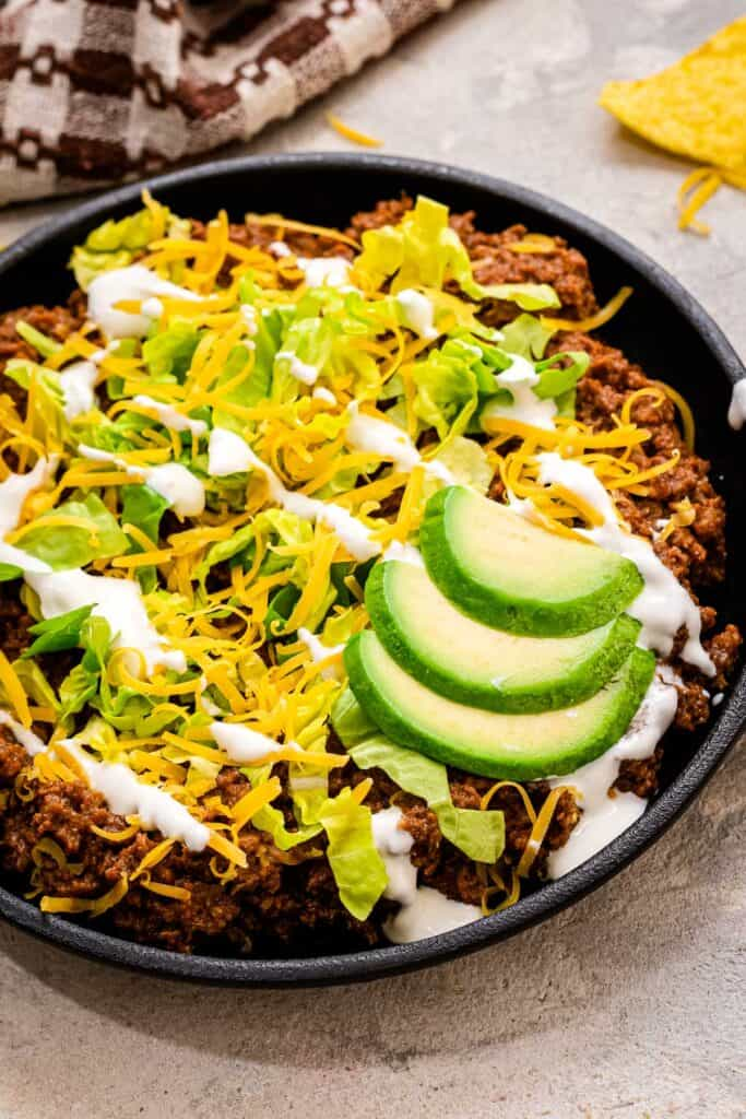 Small cast iron skillet with taco meat topped with lettuce, sour cream and avocado