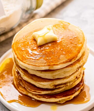 Stack of pancakes with butter and syrup on white plate
