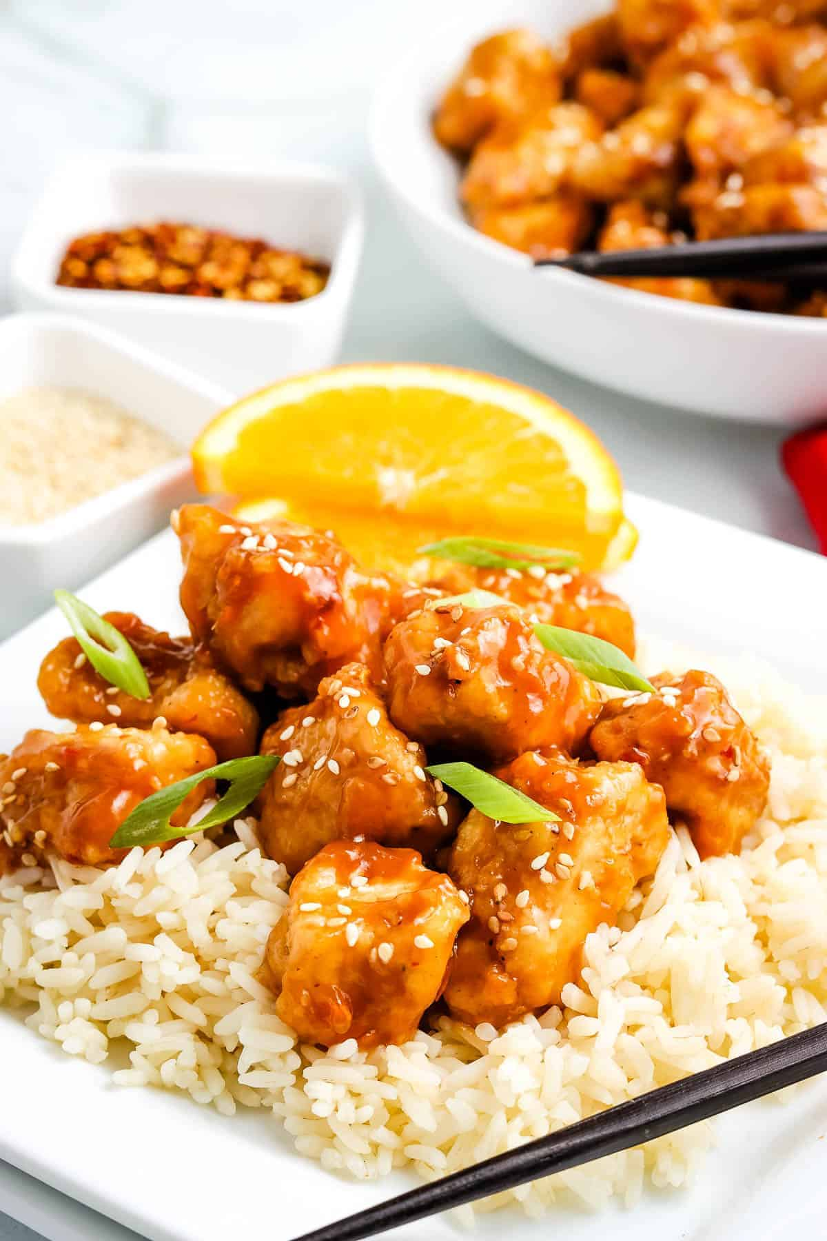 Orange chicken on top of rice on plate
