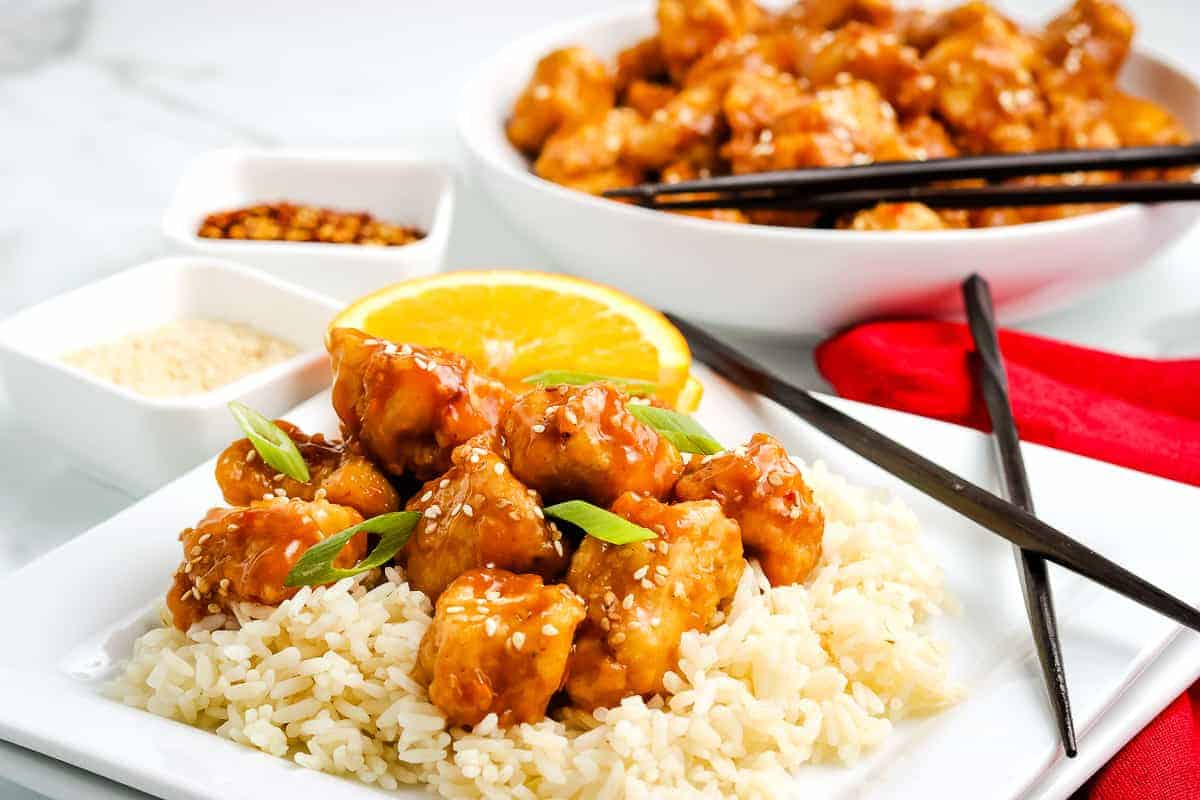Plate of rice topped with orange chicken