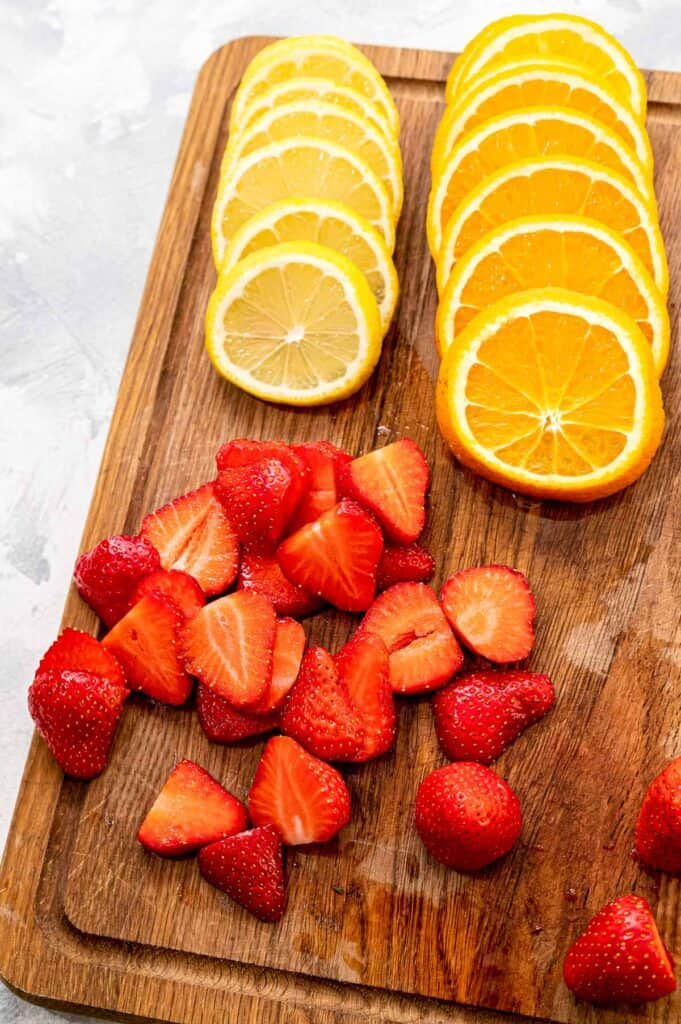 Wood cutting board with sliced lemons, oranges and strawberries