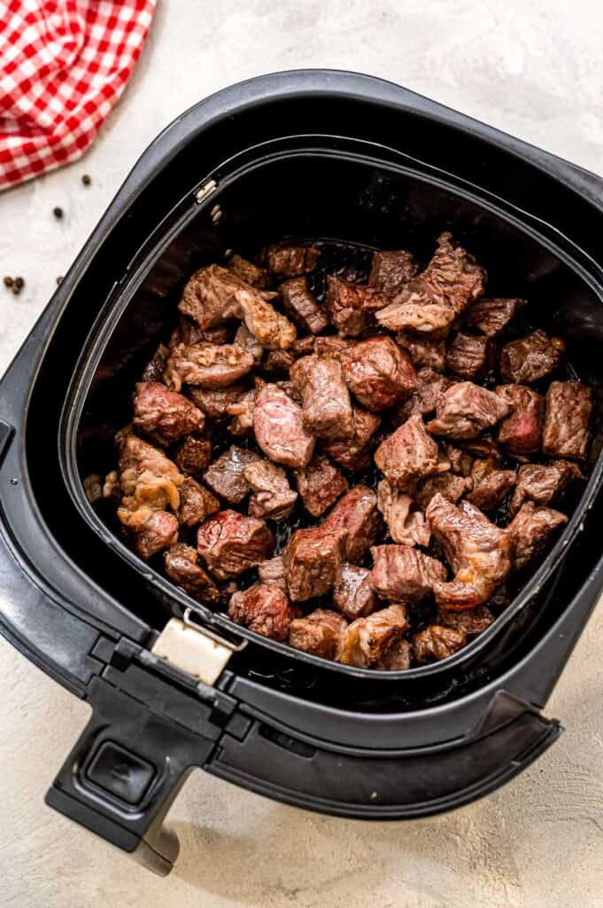 Air Fryer basket with cooked steak pieces