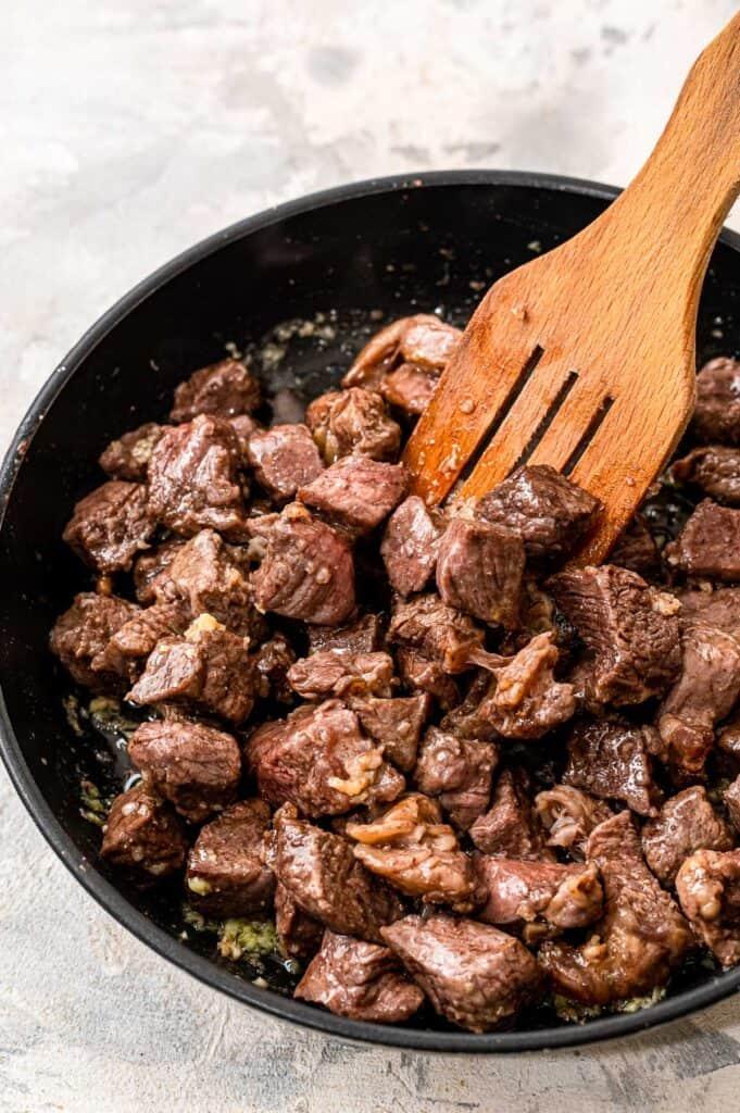 Spatula tossing steak bites in garlic butter in a skillet