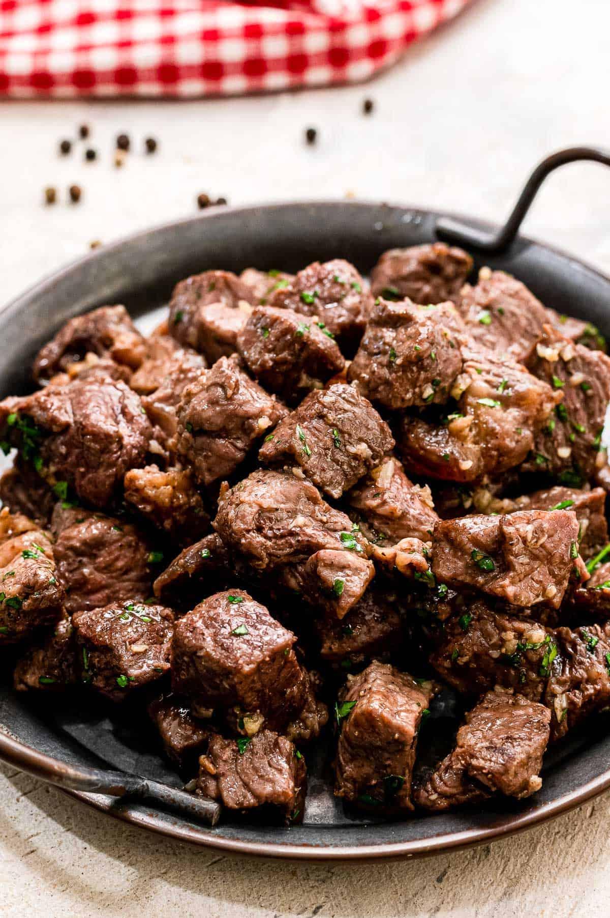 Steak Bites with Garlic Butter on black serving platter