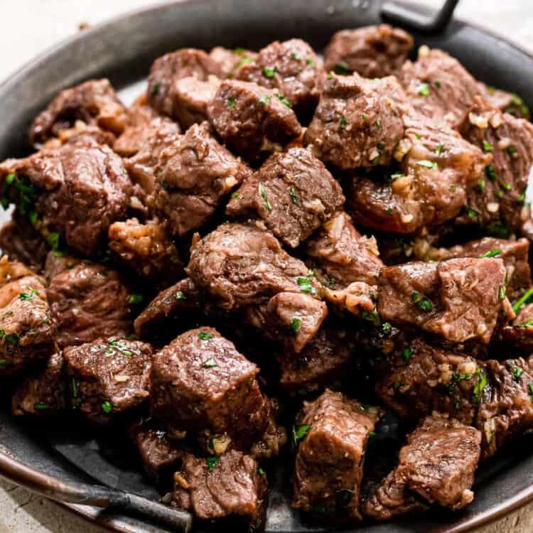Close up steak bites on black serving platter