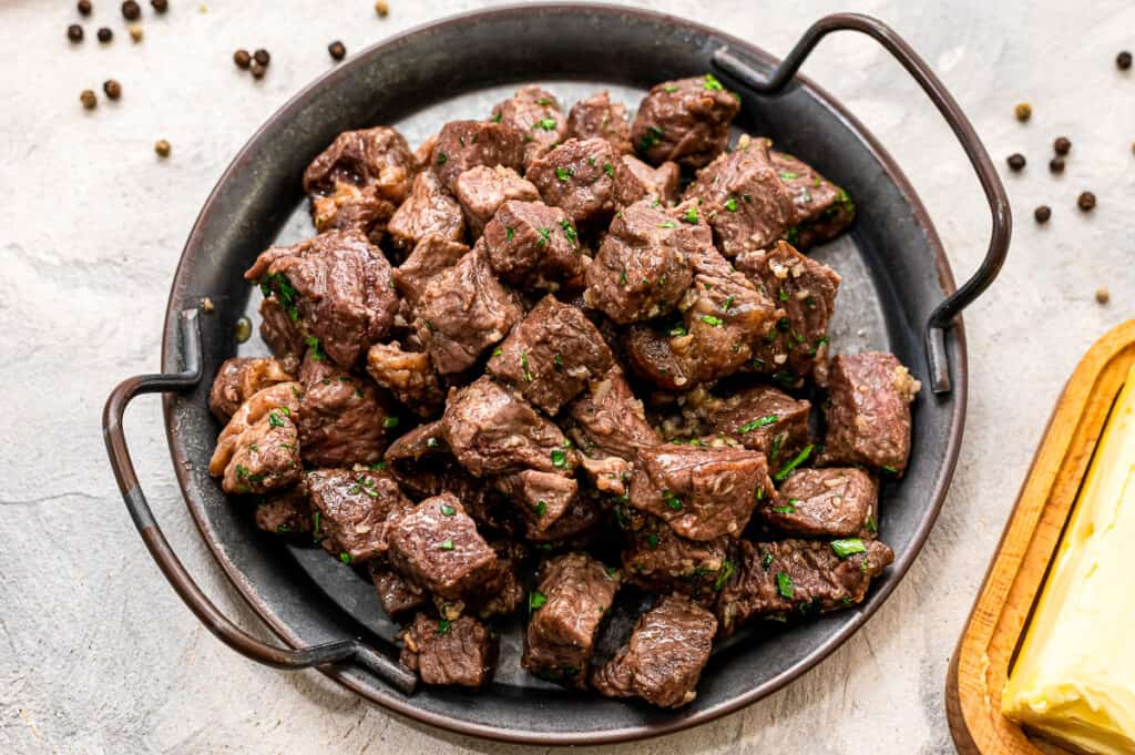 Air Fryer steak bites with garlic butter on black serving tray