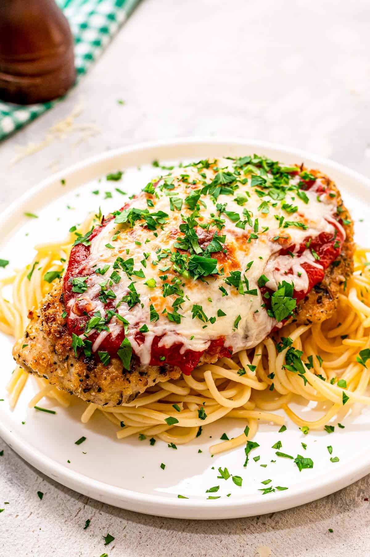 Baked Chicken Parmesan on a bed spaghetti on a white plate