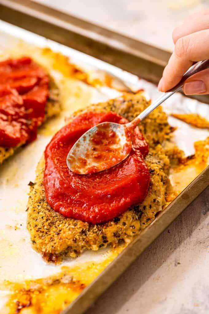 Spoon spreading marinara sauce over breaded chicken breast
