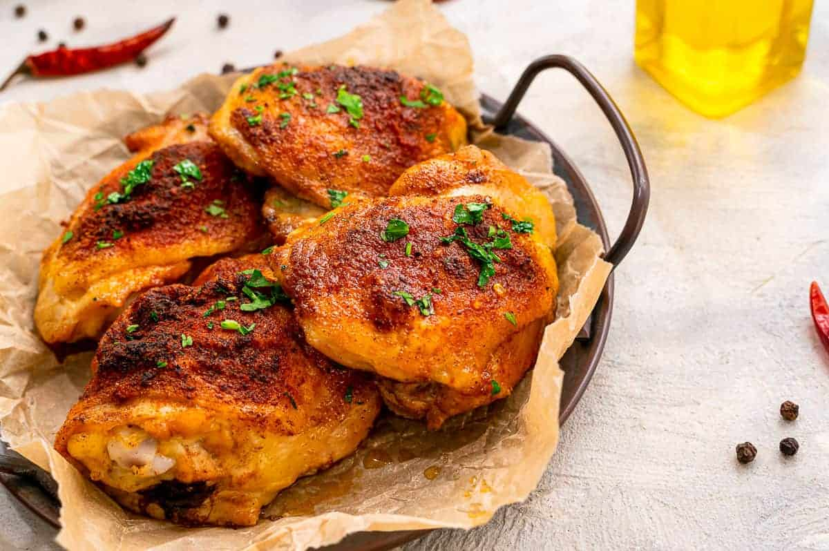 Serving tray with baked chicken thighs on it