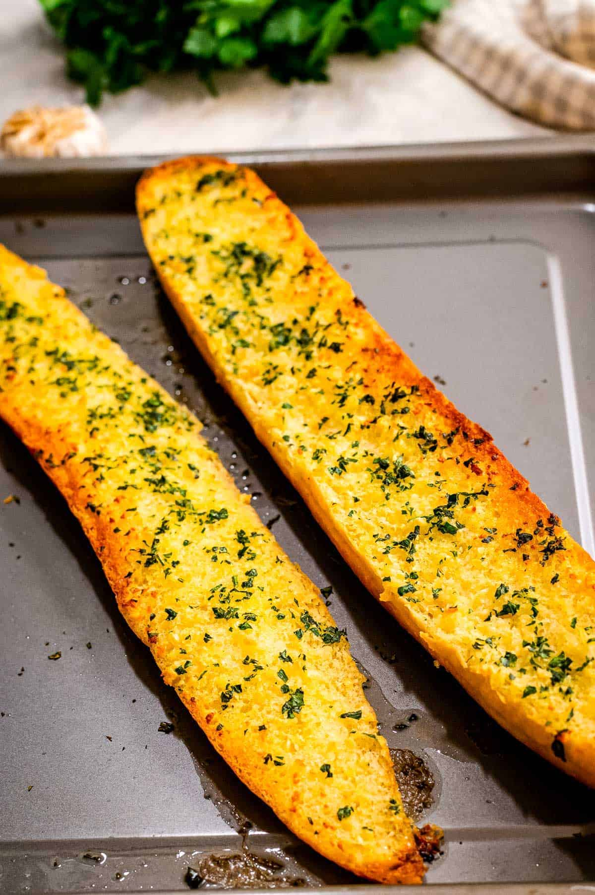 Two halves of French Bread baked with garlic butter on sheet pan