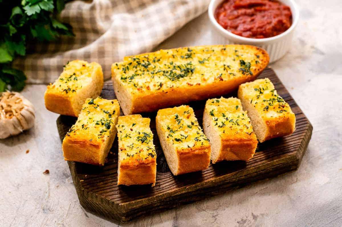 Homemade Garlic Bread pieces on a wood cutting board
