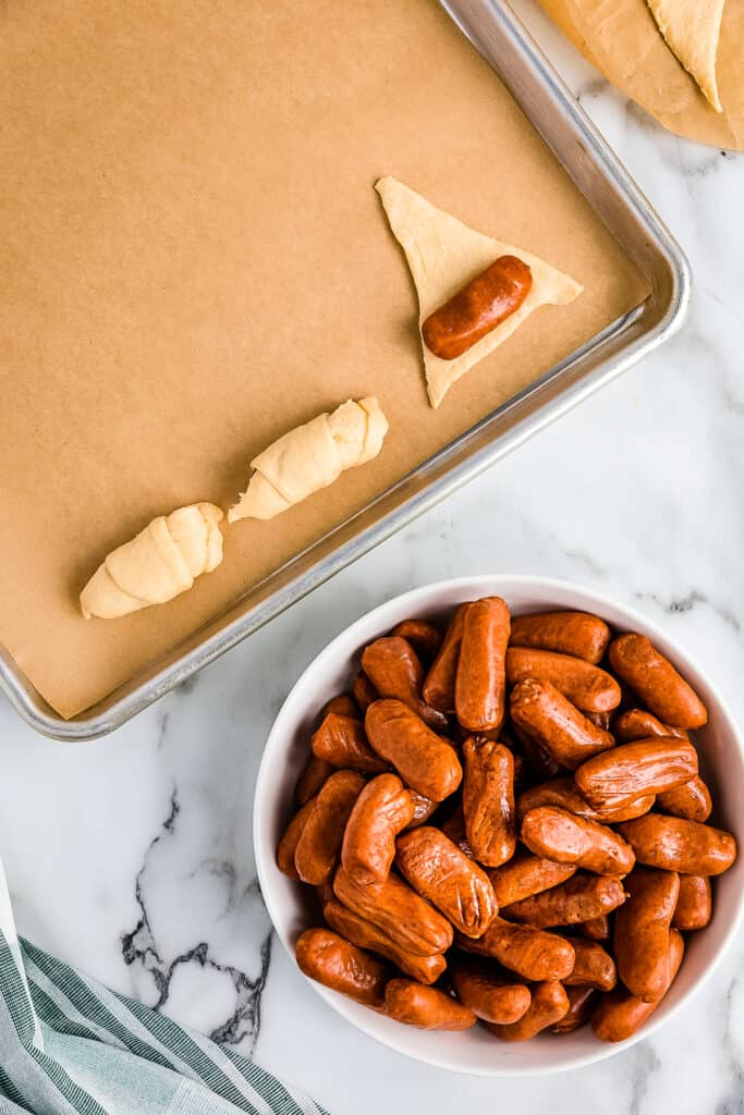 Rolling a cocktail Weiner in a crescent roll