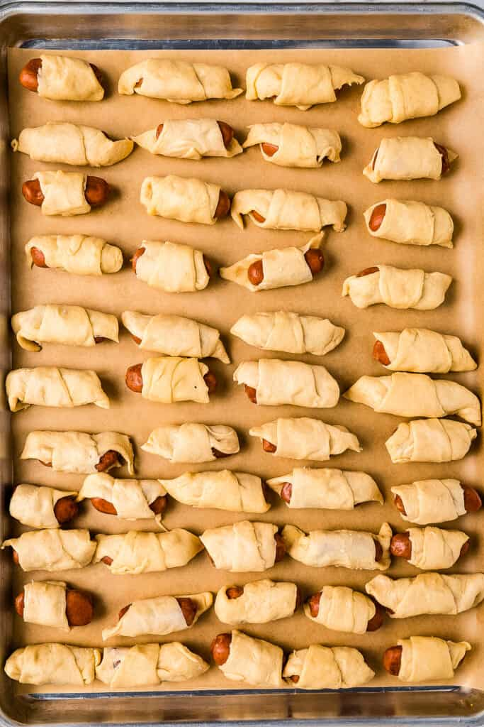 An overhead image of unbaked pigs in a blanket on sheet pan