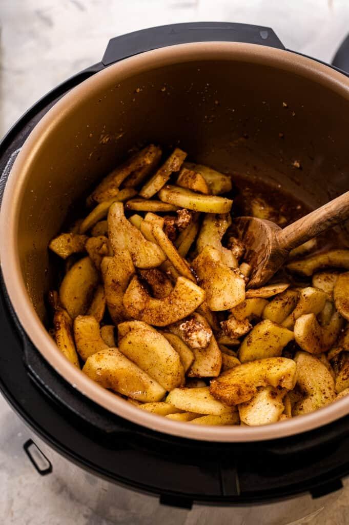 Wooden spoon stirring cinnamon apples ingredients in Instant Pot