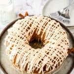 Pumpkin Bundt Cake with a drizzle of cream cheese frosting on cake stand