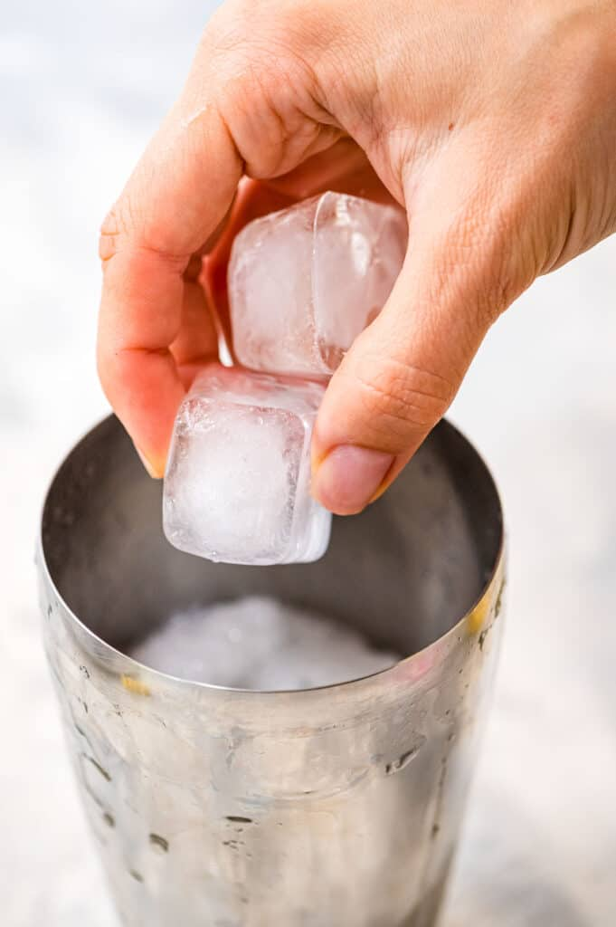 Placing ice cubes into cocktail shaker