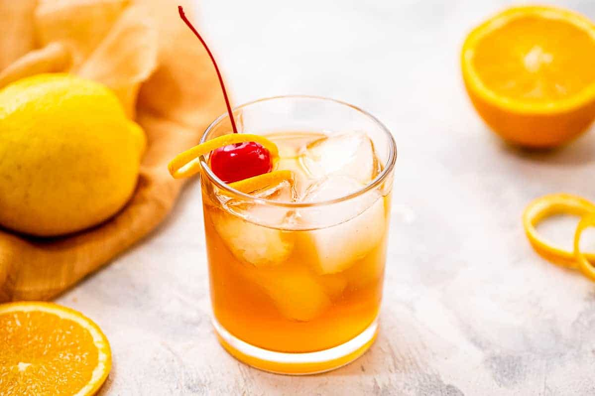 Cocktail glass with whiskey sour in it and garnished with maraschino cherry and orange peel