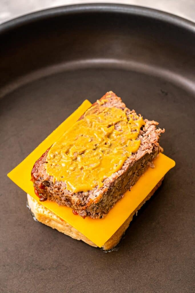 Skillet with bread, cheese and leftover meatloaf slice