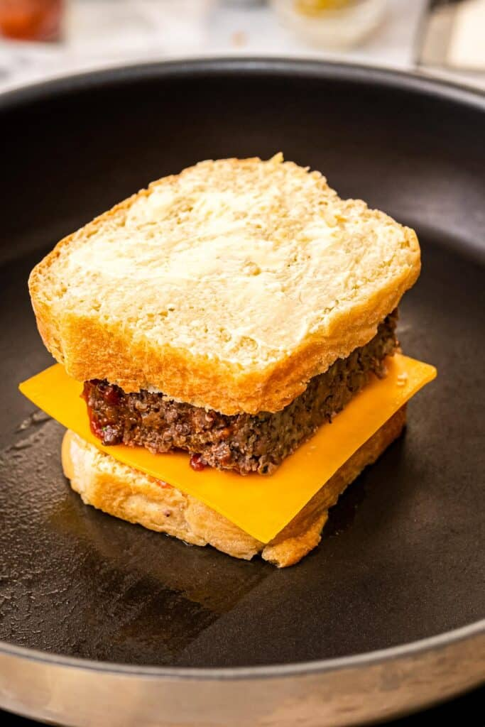 Skillet with bread, cheese, slice of meatloaf and another slice of bread