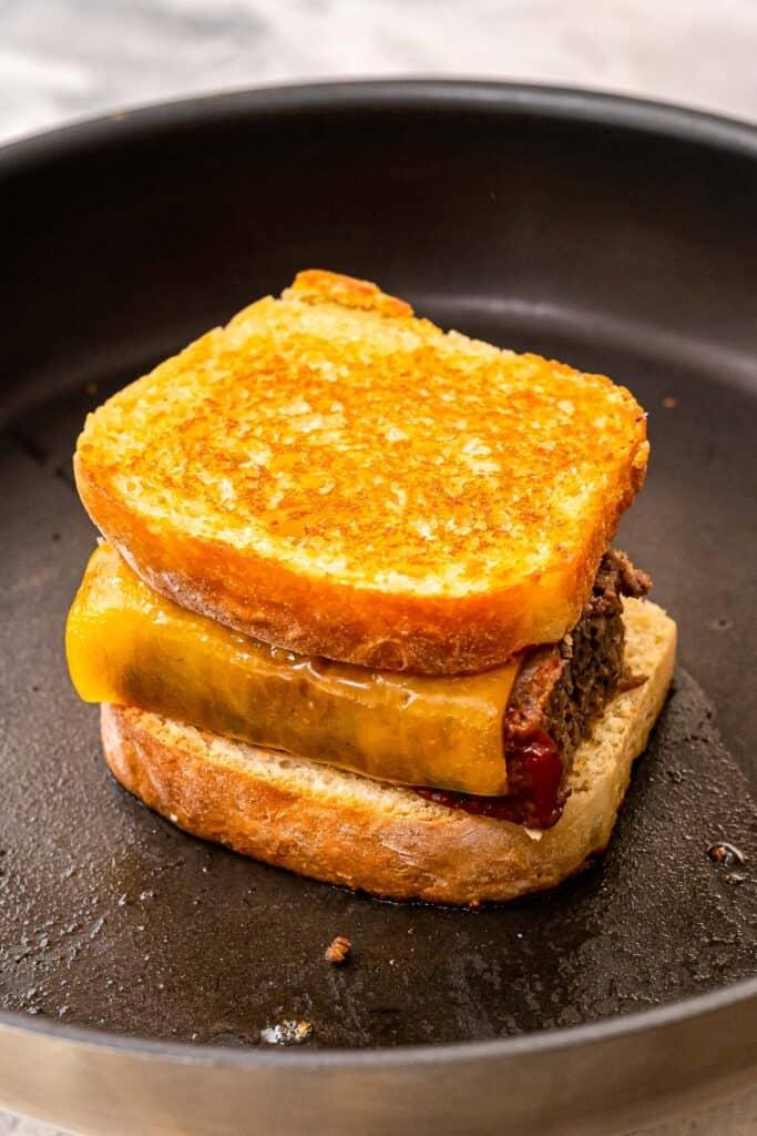 Toasted meatloaf sandwich in skillet