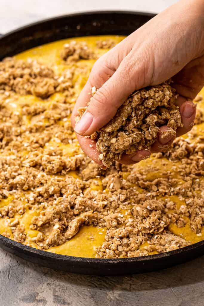 Hand sprinkling streusel topping over pumpkin filling