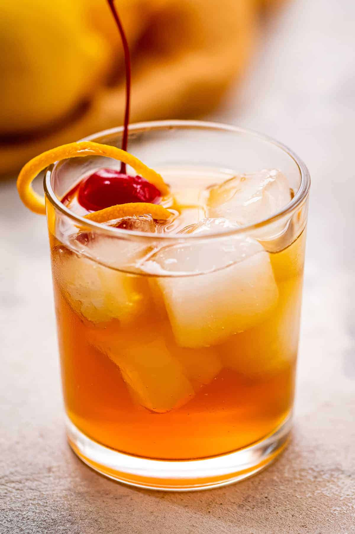 Glass with whiskey sour garnished with orange peel and maraschino cherry